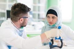 Étudiants arabes avec le hijab tout en travaillant au dentier, dents fausses photos libres de droits