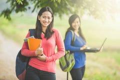 Étudiants asiatiques avec son ami se tenant au holdin de fond Images stock