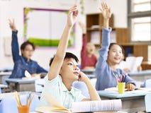 Étudiants asiatiques d'école primaire soulevant des mains dans la classe image stock