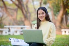 Étudiants asiatiques de femmes souriant et s'asseyant sur le gree Photo stock