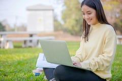 Étudiants asiatiques de femmes souriant et s'asseyant sur le gree Photographie stock libre de droits
