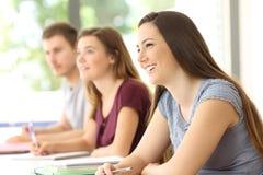 Étudiants attentifs écoutant dans une salle de classe Images libres de droits