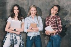 Étudiants attirants avec des cahiers et ordinateur portable se tenant au mur Images stock