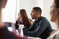 Étudiants aux bureaux assistant à la conférence sur le campus images libres de droits