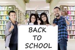 Étudiants avec de nouveau au mot d'école sur le tableau blanc Images stock