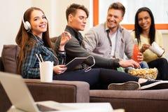 Étudiants avec des boissons et maïs éclaté dans l'intérieur à la maison Photos stock