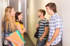 Étudiants avec des dossiers se tenant au couloir d'université Photographie stock libre de droits