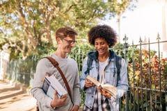Étudiants avec des livres marchant dehors sur la route Photo libre de droits