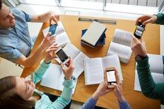 Étudiants avec des smartphones faisant des aide-mémoire Image libre de droits