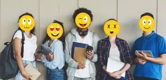 Étudiants avec des visages d'emoji tenant des livres au-dessus de fond gris photographie stock