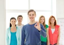 Étudiants avec l'adolescent dans l'avant montrant le signe correct Photo stock
