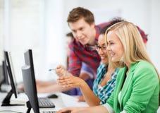 Étudiants avec l'ordinateur étudiant à l'école Images libres de droits