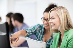 Étudiants avec l'ordinateur étudiant à l'école Photo stock