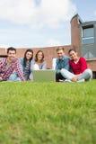 Étudiants avec l'ordinateur portable dans la pelouse contre le bâtiment d'université Photographie stock libre de droits