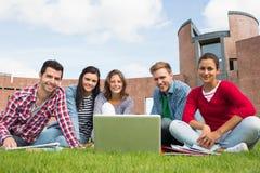 Étudiants avec l'ordinateur portable dans la pelouse contre le bâtiment d'université Image stock