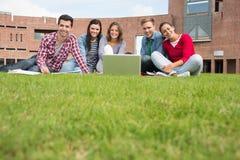 Étudiants avec l'ordinateur portable dans la pelouse contre le bâtiment d'université Photos libres de droits