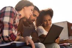 Étudiants avec l'ordinateur portable dans le campus photos stock