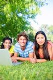 Étudiants avec l'ordinateur portable se trouvant sur le campus Photo libre de droits