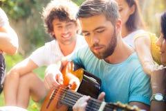 Étudiants avec la guitare se reposant dehors Photo stock