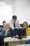 Étudiants avec le professeur dans le classrom de laboratoire d'ordinateur Photo stock