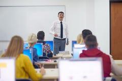 Étudiants avec le professeur dans le classrom de laboratoire d'ordinateur Image stock