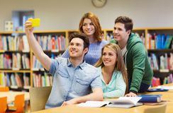 Étudiants avec le smartphone prenant le selfie à la bibliothèque Photographie stock libre de droits