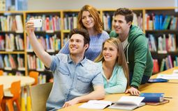 Étudiants avec le smartphone prenant le selfie dans la bibliothèque Images stock