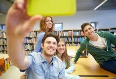Étudiants avec le smartphone prenant le selfie dans la bibliothèque Image libre de droits