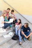 Étudiants ayant l'amusement avec des escaliers d'école d'ordinateur portatif Photos libres de droits