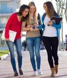 Étudiants ayant l'amusement avec des smartphones après classe Photos libres de droits