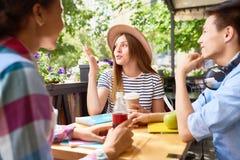 Étudiants causant au déjeuner en café extérieur Photographie stock libre de droits