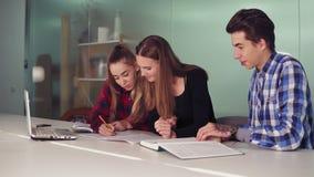 Étudiants concentrés travaillant à leur travail se reposant ensemble à la table et au café potable le groupe d'appareil-photo a i banque de vidéos