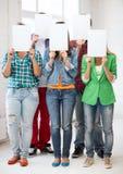 Étudiants couvrant des visages de papiers blancs Image libre de droits