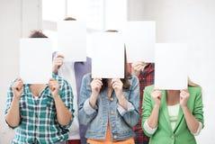 Étudiants couvrant des visages de papiers blancs Images libres de droits