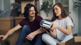 Étudiants déballant dans le nouvel appartement prenant des choses de la boîte parlant pendant la relocalisation banque de vidéos
