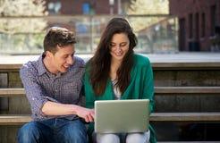 Étudiants détendant et travaillant sur l'ordinateur portable dehors Photographie stock libre de droits