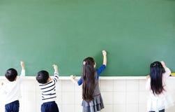 étudiants d'école dessinant sur le tableau image stock