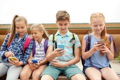 Étudiants d'école primaire avec des smartphones Image stock
