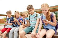 Étudiants d'école primaire avec des smartphones Photographie stock