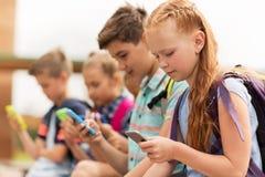 Étudiants d'école primaire avec des smartphones Images libres de droits