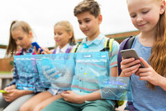 Étudiants d'école primaire avec des smartphones Photographie stock libre de droits