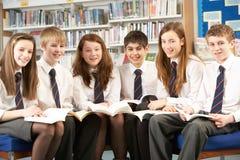 Étudiants d'adolescent dans des livres du relevé de bibliothèque Image stock