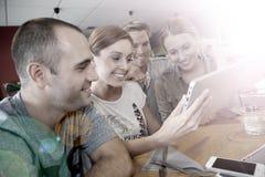 Étudiants d'amis appréciant en snack-bar utilisant un comprimé Photographie stock libre de droits