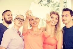 Étudiants d'amis prenant la photo d'individu avec le comprimé Photo libre de droits
