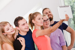 Étudiants d'amis prenant la photo d'individu avec le comprimé Image stock