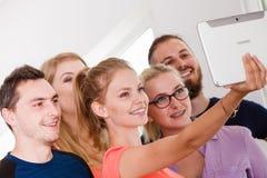 Étudiants d'amis prenant la photo d'individu avec le comprimé Photographie stock