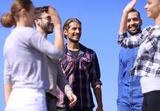 Étudiants d'amis se donnant de hauts cinq Photographie stock libre de droits