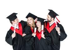 Étudiants dans des chapeaux scolaires se tenant embrassants avec des diplômes Images stock