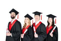 Étudiants dans des robes d'obtention du diplôme et taloches tenant des diplômes sur le blanc Photographie stock