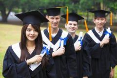 étudiants dans des robes d'obtention du diplôme sur le campus universitaire Photos stock